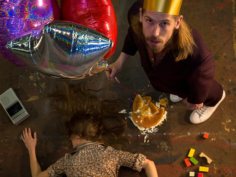 John is wearing a crown and holding ballons over Solene who is lying face down on the ground